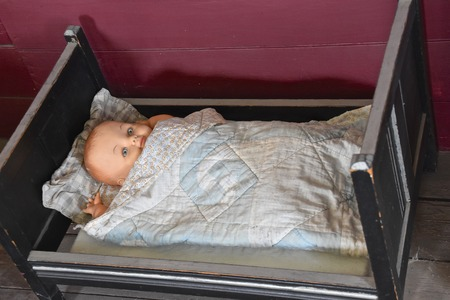 A child's very old doll lies in a small wooden bed wrapped in a blanket