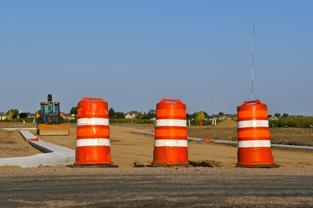 Orange barrels in a construction zone prevents traffic through a new roadway which only has curbs and gutters in place.
