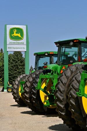 KINDRED, PÓŁNOCNA DAKOTA, 21 sierpnia 2018 r.; Ciągniki i znaki John Deere są produktami John Deere Co, amerykańskiej korporacji produkującej maszyny rolnicze, budowlane, leśne, silniki wysokoprężne i układy napędowe Publikacyjne