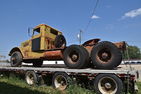 The cab and chassis of an old yellow truck semi is loaded on the platform of a trailer.