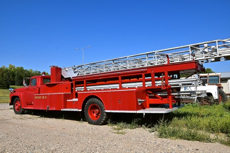 An old fire truck with long ladder and 911 emergency call number Фото со стока