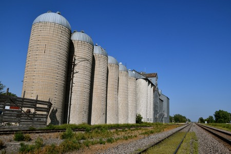 A huge elevator system with with a row of stave silos for holding grain located alongside railroad tracks for transportation Фото со стока