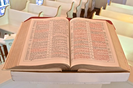 A huge old bible  opened to the Book of James rests on a pulpit in a small chapel