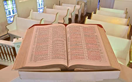A huge old bible  opened to the Book of John rests on a pulpit in a small chapel