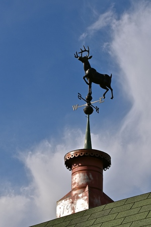 A wind vane with a running buck deer anchored to a cupola is silhouetted n the sky Stok Fotoğraf