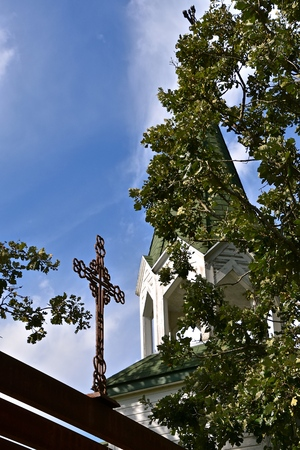 A metal cross on a beam is flanked by the partially hidden steeple on a white church.