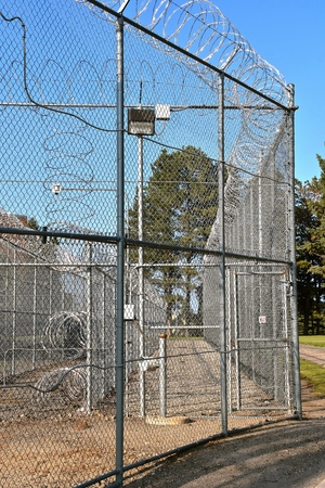 A camera and security concentina fence surround a prison facility 写真素材 - 110834502