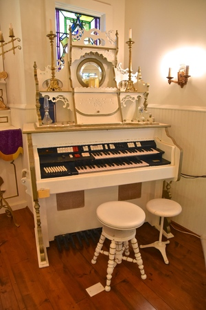 A white  electronic piano or organ with several antique circular spinning stools in a church