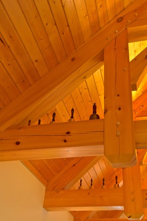 Musical hand bells are displayed in the rafters and support beams of a church 写真素材