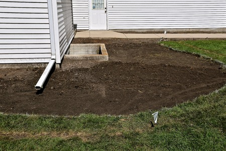 Sod has been removed for landscaping around the foundation of a house.