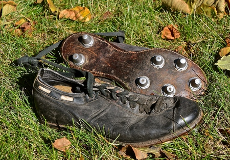 An old pair of leather football shoes with metal cleats for traction Stock Photo