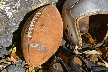 An old leather football, helmet and a pair of cleated shoes shoes bring back  the autumn memories of a past era of the gridiron.