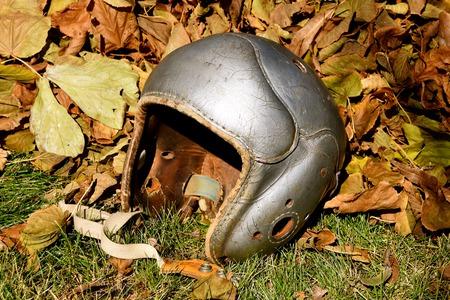 An old vintage football helmet is left laying in the autumn leaves 版權商用圖片