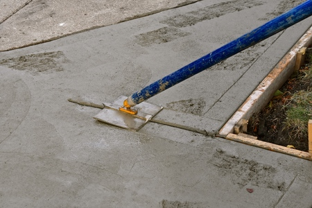 A concrete laborer screeds wet concrete on a sidewalk repair project Stock Photo