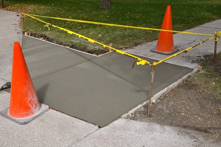Des cônes et un ruban jaune d'avertissement entourent un projet de réparation terminé sur un trottoir et une allée. Banque d'images
