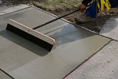 A concrete laborer brooms wet concrete on a sidewalk repair project.