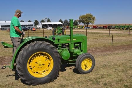 PEKIN, NORTH DAKOTA, September 2, 2018:  The operator of an antique D John Deere  is joining the lineup  tractor during the  Labor Day Stump Lake Village Threshing Bee. Editöryel