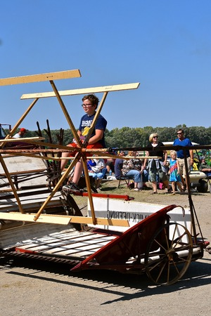 PEKIN, NORTH DAKOTA, September 2, 2018: An unidentified  young man rides an old McCormick Deering grain binder at the Labor Day Stump Lake Village Threshing Bee parade. 写真素材 - 114869409