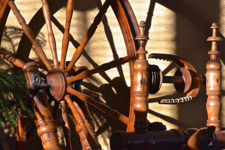 A closeup of a very old wheel  and spokes of a hand crafted spinning wheel