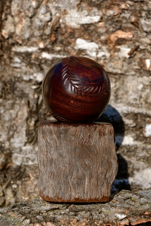 A carved baseball from  a chunk of walnut with stitche