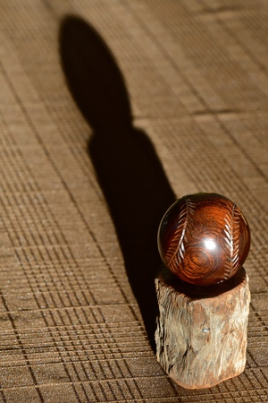 A carved baseball from  a chunk of walnut with stitches cast s a long shadow.