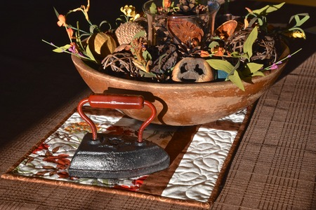 An old metal flat iron shares decorating space with a wooden bowl of guards and fall items.