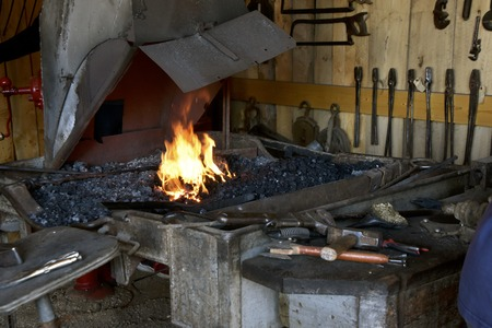 Flames from a red hot forge and tools laying on a workbench are found in a blacksmith shop