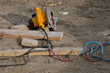 A skill saw hooked up to a heavy electrical cord is left on the ground at a construction site.