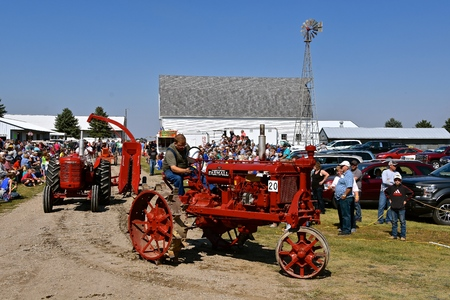 PEKIN, NORTH DAKOTA, September 2, 2018: An old restored F-12 Farmall red  tractor  participates in a parade during the Labor Day Stump Lake Village Threshing Bee.