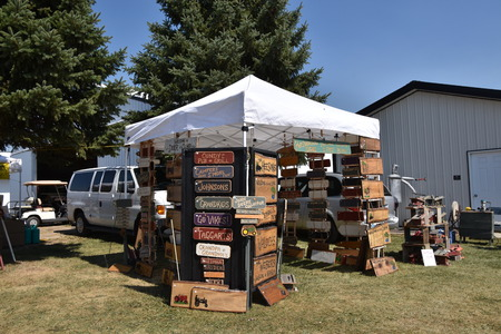 PEKIN, NORTH DAKOTA, September 2, 2018: A booth and canopy of carved routed signs  is displayed at the flea market  of  the Stump Lake Village Threshing Bee during Labor Day weekend. Editöryel