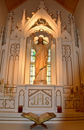 A statue of Jesus Christ of Nazareth stands in a chapel with an open Bible  by the altar below.