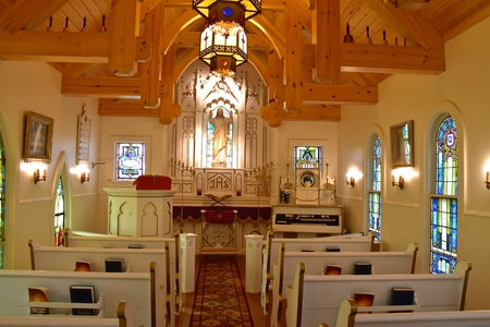 The inside of a small chapel with an image of Jesus Christ by the altar.