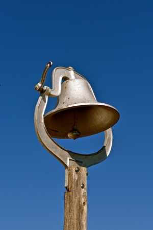 An old bell on a post was once used at a real one room schoolhouse to inform students classes are to start.