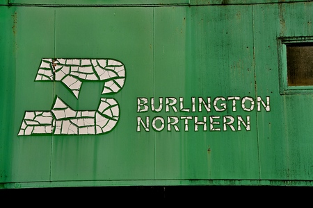 PEKIN, NORTH DAKOTA, September 1, 29018: The  old peeling BN logo on the side of the green caboose was once property of Burlington Northern which has since become BNSF, part of Berkshire Hathaway subsidiary.