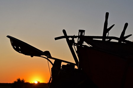 The seat, levers, and gears of an farming machines silhouetted in the early morning sunrise