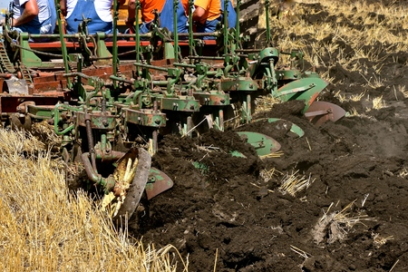 A group of unidentified men in bib overalls sit a a gang plow  in a wheat stubble field. Reklamní fotografie