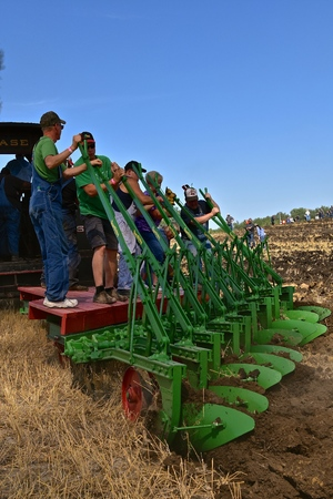 ROLLAG, MINNESOTA, September 1, 2018: Unidentified volunteers ride a gang plow pulled by a steam engine in field demonstrations at the annual WCSTR farm threshers reunion in Rollag held each labor Day weekend where thousands attend.