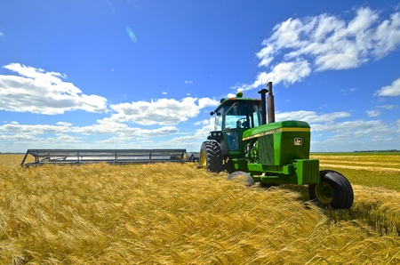 ENDERLIN, NORTH DAKOTA, July 27, 2015: Deere and Company is the largest agricultural machinery producing company in the world and as seen in this wheat field, the green and yellow 4440 tractor and swather is a trademark color. 新闻类图片