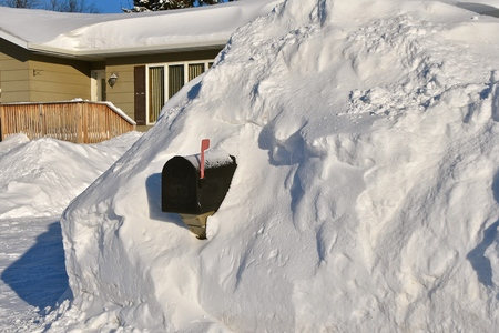 Mailbox nearly  buried in a snowdrift required digging to receive the daily mail after a snowstorm.