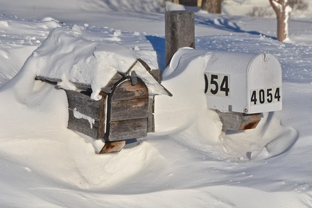 Mailboxes nearly  buried in a snowdrift require digging to receive the daily mail after a snowstorm.