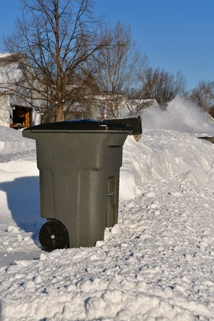 A plastic garage can sits on the curb awaiting pickup surrounded by snow and snowplowing in the distance.