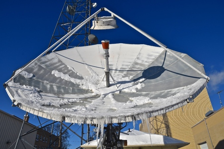 A communications dish for transmitting signals is partially covered with ice and hanging icicles.