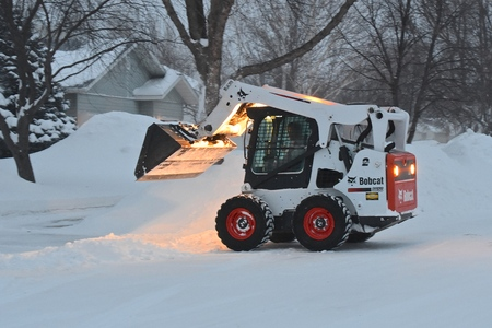 MOORHEAD, MINNESOTA, February 6, 2019: The S650 Bobcat skid steer removing driveway snow is headquartered in West Fargo, North Dakota.