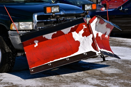 A blade for removing snow is attached to the front end of a 4-wheel drive pickup. Archivio Fotografico