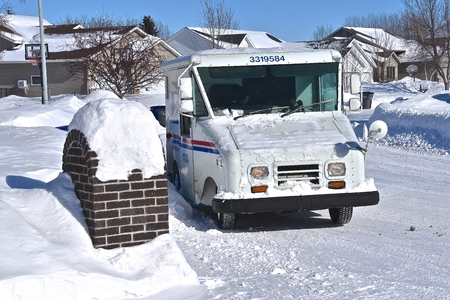 MOORHEAD, MINNESOTA, February15, 2019: The mail carrier delivers daily mail  in a snow covered neighborhood with a vehicle from the United States Postal System(USPS).