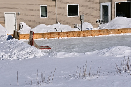 An outdoor hockey rink has been created in the backyard of a home.