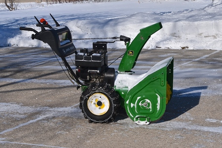MOORHEAD, MINNESOTA, February 13, 2019: The parked snow blower after cleaning a driveway was made from John Deere Co, an American corporation that manufactures agricultural, construction, forestry machinery, diesel engines, and drivetrains