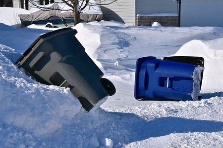 A garbage trash barrel and recycling bin are left turned over in the snow after being emptied from curbside pickup.