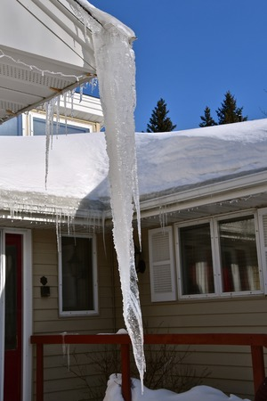 A huge icicle hangs from an eavestrough of a home. Stock Photo