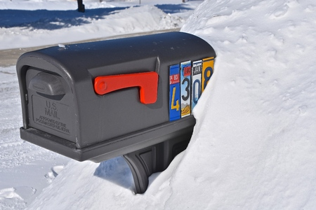 MOORHEAD, MIINNESOTA, February 13, 2019: A mailbox buried in a snowdrift displays house numbers with old license plate numbers bears a USPS on the door lid. Editorial